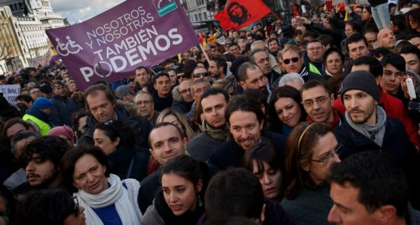 Pablo Iglesias with Juan Carlos Monedero, center right, leader of Spanish Podemos (We Can) left-wing party, smiles as he marches to give a speech at the main square of Madrid during a Podemos (We Can) party march in Madrid, Spain, Saturday, Jan. 31, 2015